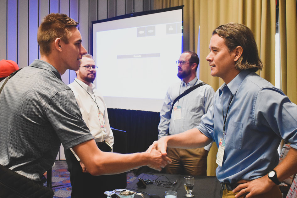 Doug Parsons shakes hands with an attendee after Podcast, Cli-Fi, and Science Storytelling for Climate Action in the Built Environment