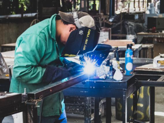 A CAPLA student welding a piece of metal on to an architecture structure