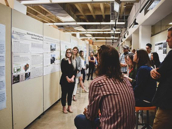 A student in the SBE program presents a project poster to faculty and studnets