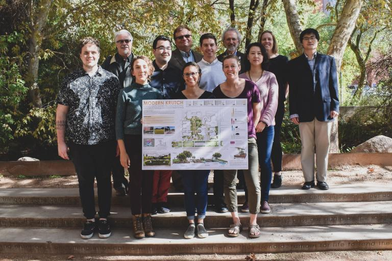 Students and jury members stand in the Underwood garden with project poster.