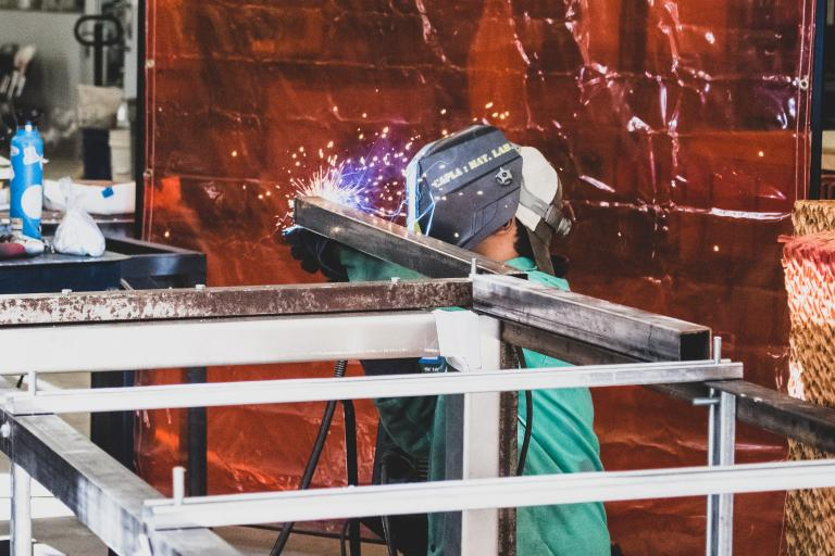 A student welding metal in the materials lab