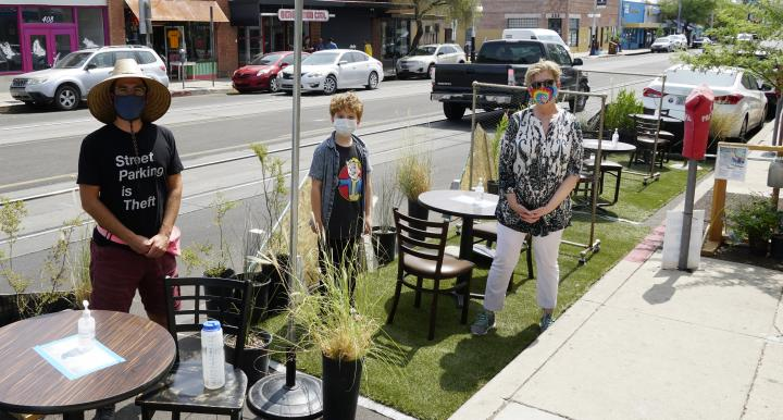 Three visitors stand in the temporary Parking Day parklet on Tucson's Fourth Avenue