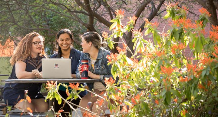 CAPLA students with laptop in Underwood Garden